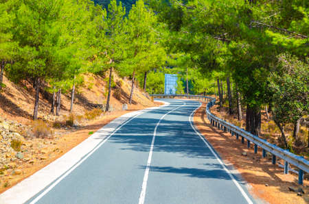 Asphalt serpentine road in Troodos mountain range with roadside fence and trees, Cyprus 免版税图像