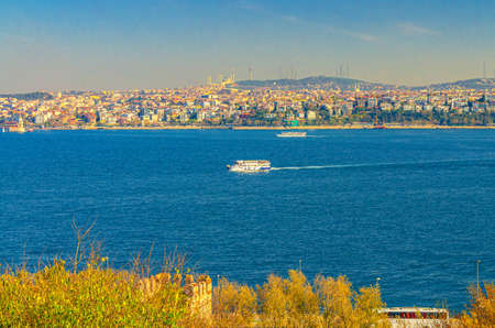 Cityscape of Istanbul city historical center with ship boat sailing water of Bosporus Bosphorus Strait of Istanbul and Doganc lar district background, Turkey
