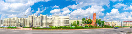 Panorama of Independence Square in Minsk city center with Government House and Saints Simon and Helena Roman Catholic church or Red Church, blue sky in sunny summer day, Republic of Belarus