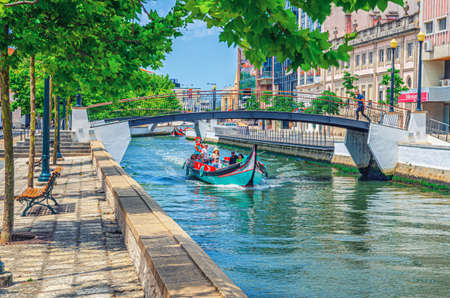 Aveiro, Portugal, June 13, 2017: traditional colorful Moliceiro boat with tourists sailing in narrow water canal, bridge across waterway and buildings along embankment promenade in city center 新闻类图片