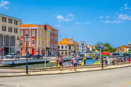 Aveiro, Portugal, June 13, 2017: people tourists walking down embankment promenade near narrow water canal and typical colorful buildings in Aveiro historical city center, blue sky background
