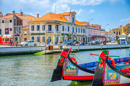 Aveiro, Portugal, June 13, 2017: traditional colorful Moliceiro boat mooring in water canal in Aveiro city historical center, sunny summer day, typical buildings and blue sky background 新闻类图片