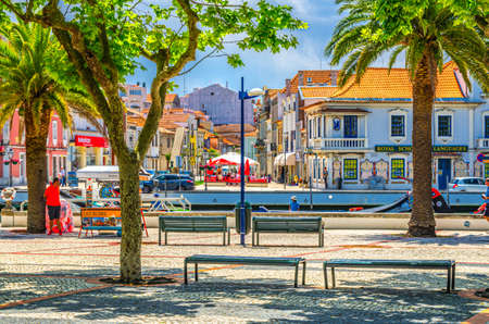 Aveiro, Portugal, June 13, 2017: Aveiro city historical center with embankment promenade of narrow water canal with benches and palm trees, sunny summer day, typical buildings and blue sky background 新闻类图片
