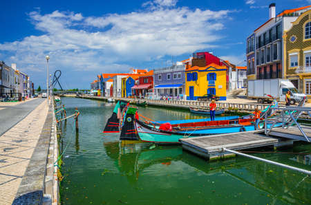 Aveiro, Portugal, June 13, 2017: traditional colorful Moliceiro boat mooring in narrow water canal in Aveiro city historical center with typical colorful buildings, blue sky background 新闻类图片