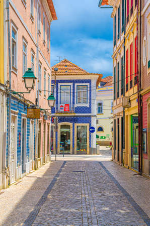 Aveiro, Portugal, June 13, 2017: typical colorful azulejos-tiled buildings houses in cobblestone street of Aveiro city historical center in sunny summer day, blue sky background 新闻类图片