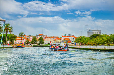 Aveiro, Portugal, June 13, 2017: traditional colorful Moliceiro boat with tourists sailing in narrow water canal along embankment promenade in historical city center