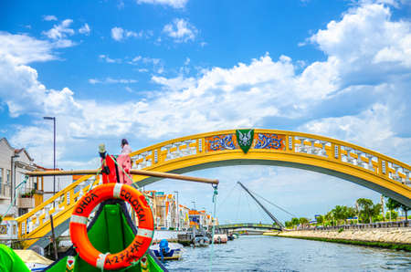 Aveiro, Portugal, June 13, 2017: nose of traditional colorful Moliceiro boat in narrow water canal, bridge across waterway and buildings along embankment promenade in city center, blue sky background