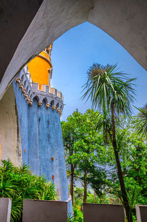 Sintra, Portugal, June 14, 2017: Pena Palace with colorful stone walls and green trees, Palacio Nacional da Pena Romanticist castle in Sao Pedro de Penaferrim, vertical view through arch 新闻类图片