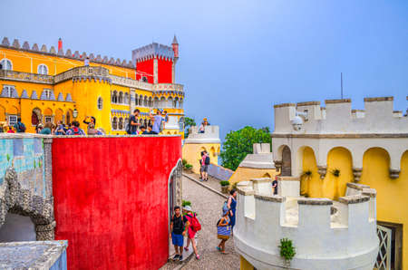 Sintra, Portugal, June 14, 2017: people tourists in Pena Palace with colorful stone walls and merlons on towers, Palacio Nacional da Pena Romanticist castle in Sao Pedro de Penaferrim 新闻类图片