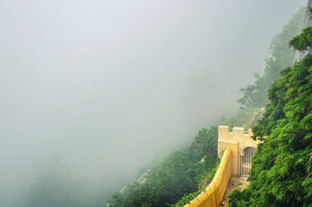 Sintra, Portugal, June 14, 2017: defense wall with gate of Pena Palace on steep slope of mountain with green forest in fog, Palacio Nacional da Pena Romanticist castle in Sao Pedro de Penaferrim