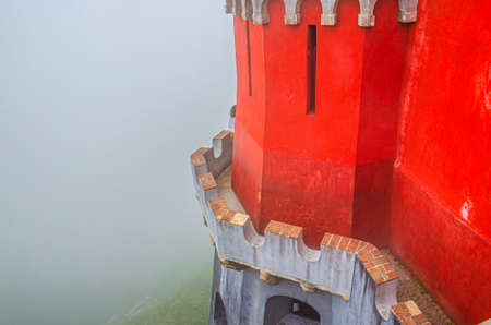Sintra, Portugal, June 14, 2017: red defense wall and tower with merlons of Pena Palace with green forest in fog background, Palacio Nacional da Pena Romanticist castle in Sao Pedro de Penaferrim