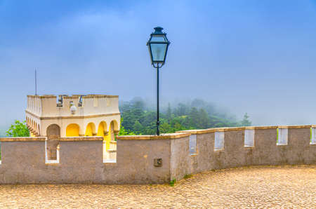 Sintra, Portugal, June 14, 2017: Iron vintage lantern lamp and merlons on tower of Pena Palace castle, green forest in fog, Palacio Nacional da Pena Romanticist castle in Sao Pedro de Penaferrim