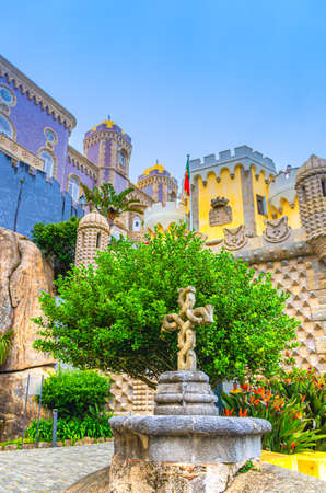 Sintra, Portugal, June 14, 2017: Pena Palace with colorful decorative walls, towers and stone cross, Palacio Nacional da Pena Romanticist castle in Sao Pedro de Penaferrim, vertical view 新闻类图片