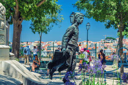 Lisbon, Portugal, June 15, 2017: statue of boy, green trees and people tourists in Miradouro de Sao Pedro de Alcantara garden park with view of historical city center