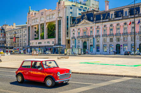 Lisbon, Portugal, June 15, 2017: red color retro vintage car riding in Restauradores Square Praca with Foz Palace Palacio and Teatro Eden building in Lisboa historical city center in sunny summer day