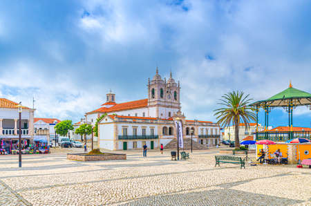 Nazare, Portugal, June 22, 2017: Sanctuary of Our Lady of Nazare catholic church and street misicians near gazebo in cobblestone square with palm trees in Sitio hilltop 新闻类图片