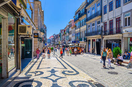 Porto, Portugal, June 23, 2017: people tourists walking down Rua de Santa Catarina cobblestone pedestrian street with colorful buildings and houses in historical city center in sunny summer day