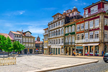 Guimaraes, Portugal, June 24, 2017: Largo do Toural square with colorful multicolored traditional typical buildings and houses in Guimaraes city historical center, blue sky background