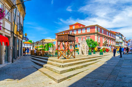 Guimaraes, Portugal, June 24, 2017: street restaurants and Court of Appeal building in Largo do Misericordia square in Guimaraes city historical center, blue sky background
