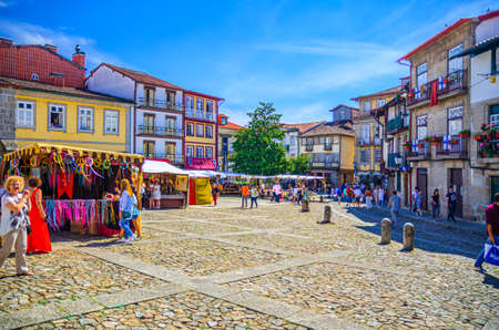 Guimaraes, Portugal, June 24, 2017: people tourists walking down cobblestone square with traditional multicolored houses in Guimaraes city historical center during celebration city day 新闻类图片