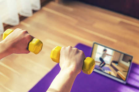 Young woman hands raising yellow dumbbells during workout sports at home, video exercises tutorials on tablet screen on floor mat in living room background, close-up view from back, sport concept