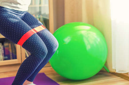 Woman legs in sport leggings doing sit-ups knees squats with red rubber resistance band during workout at home, green rubber fitness ball near bookcase and window in living room, sport concept
