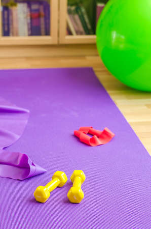 Sports equipment on floor in living room, violet yoga mat, yellow dumbbells, red rubber resistance band and green rubber fitness aerobic ball, bookcase background, home workout concept, vertical view 免版税图像