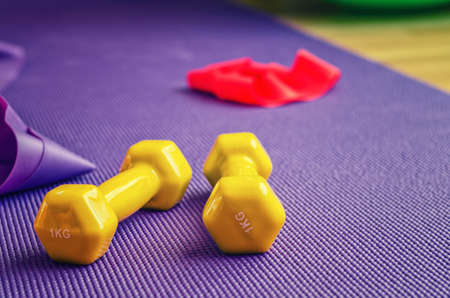 Sports equipment close-up view, yellow dumbbells and red rubber resistance band on violet ribbed yoga mat, home workout concept