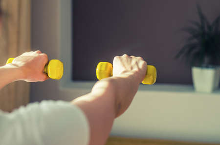Young woman arms raising yellow dumbbells during workout sports at home, flower pot with green plant in wall niche in living room background, close-up view from back, sun light from side 免版税图像