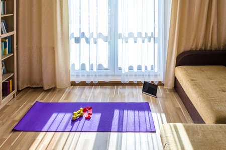Living room with sports equipment and tablet on floor, bookcase and sofa near French window, yellow dumbbells and red rubber resistance band on violet yoga mat, home sport workout concept