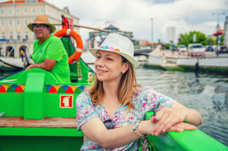 Aveiro, Portugal, June 13, 2017: Young beautiful woman traveler with hat sailing in Moliceiro traditional boat with gondolier in water canal and looking at landmarks and sights of historical centre 新闻类图片