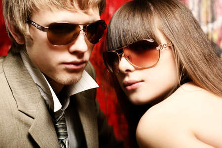 shades of grey: Fashionable young couple wearing sunglasses