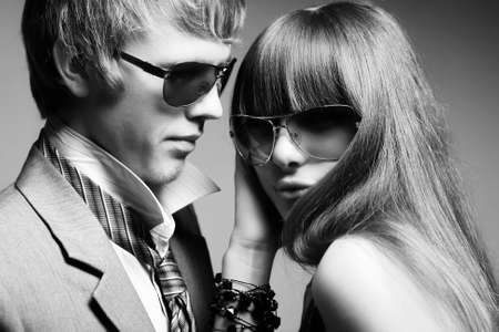 formal wear clothing: Fashionable young couple wearing sunglasses