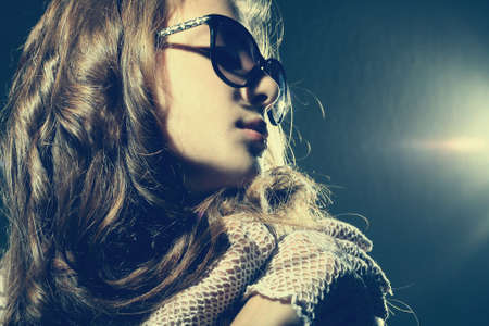 Fashion portrait of a beautiful young sexy woman wearing sunglasses  photo