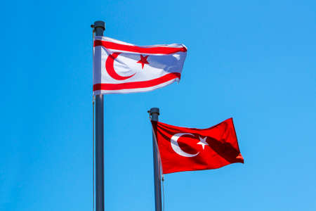 Turkish and North Cyprus flags on blue sky background
