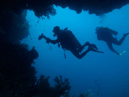 Two divers are silhouetted through cave and coral Stockfoto