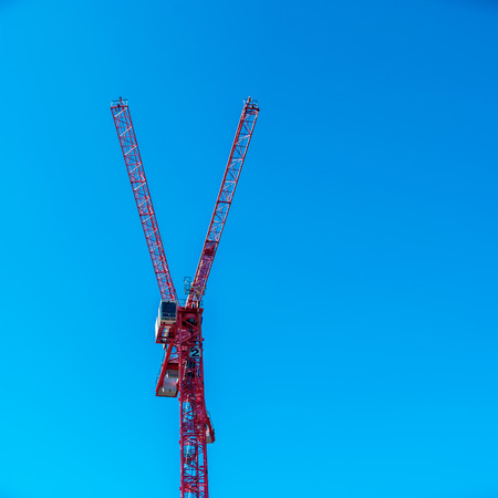 Red cranes in front of a cloudless sky representing a Y