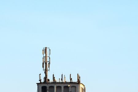 Antennae for mobile phones on a roof in front of a blue sky