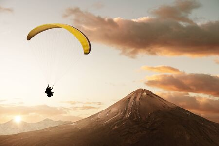 Yellow tandem paraglider enjoy freedom in scenic mountain landscape 免版税图像