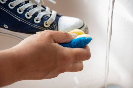 Adult is cleaning a blue laced sneaker in sink unsing a blue yellow sponge