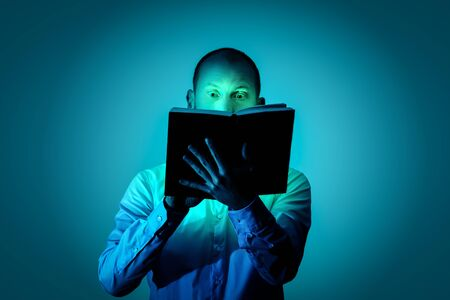 Man is fascinated by reading an exciting book and is illuminated by a magical light