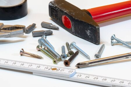 Different tools and screws on white table