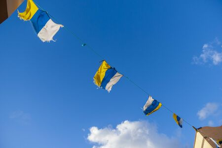 Four flags of the canary islands fluttering in the wind against blue sky