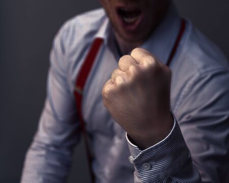 Businessman clenches his fist and is aggressive or celebrates his success