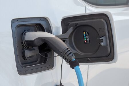 Electric car charged with plug at battery charging station