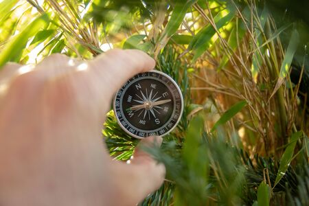 Concept of orientation in life by holding a compass in hand in front of green plants 免版税图像