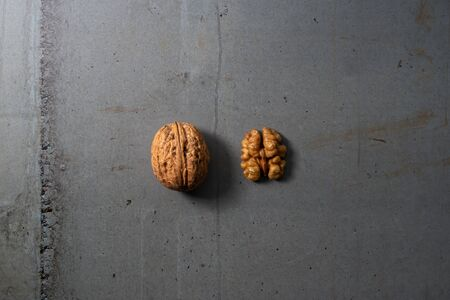 Walnut shell and kernel on grey concrete texture representing healthy food