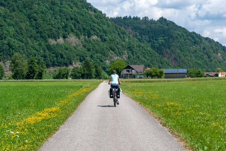 individual woman on a bike trip between mountains in a valley