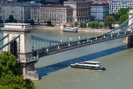 Sz chenyi Chain Bridge and tourist boat in Budapest at Danube river on a sunny day 免版税图像