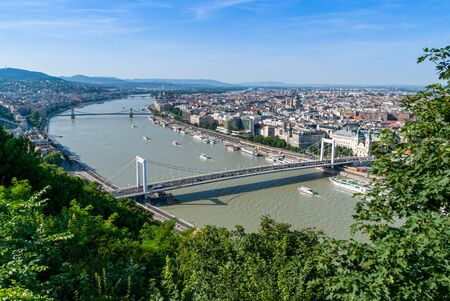 Panoramic view of Budapest at the Danube river with tourist boats on a sunny day with mountains in background